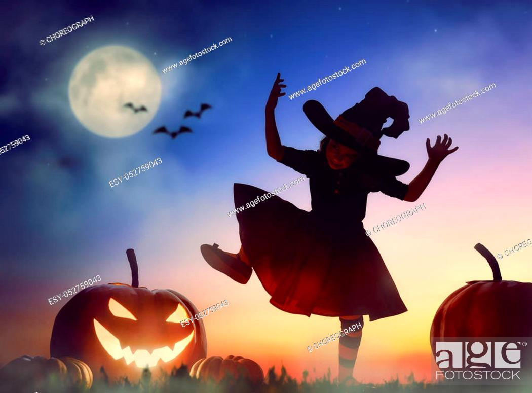 Imagen: Happy Halloween! Cute little witch with a big pumpkin. Beautiful young child girl in witch costume outdoors.