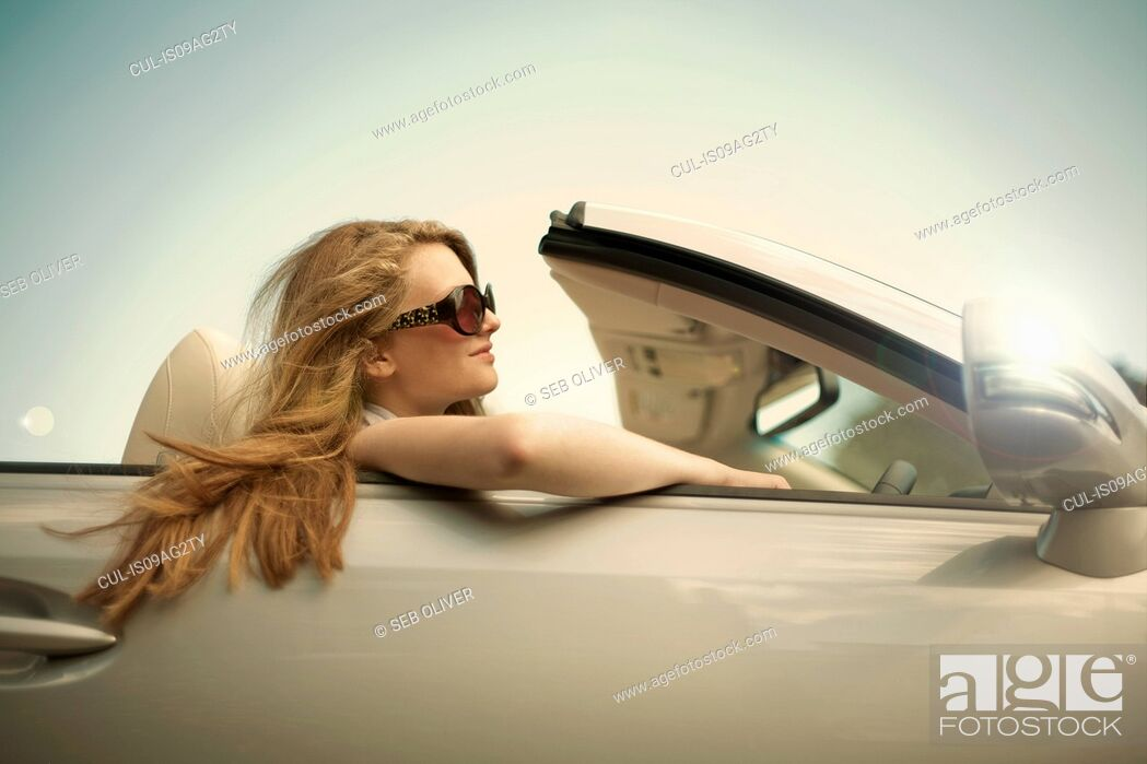 Stock Photo: Teenage girl showing off in sports convertible.