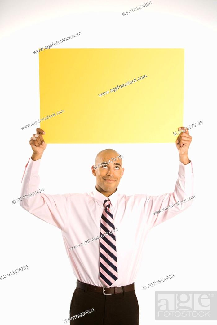 Stock Photo: Man holding blank yellow sign overhead standing against white background.