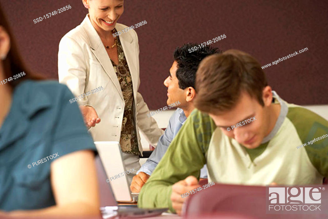 Stock Photo: Professor and a college student looking at each other and smiling.