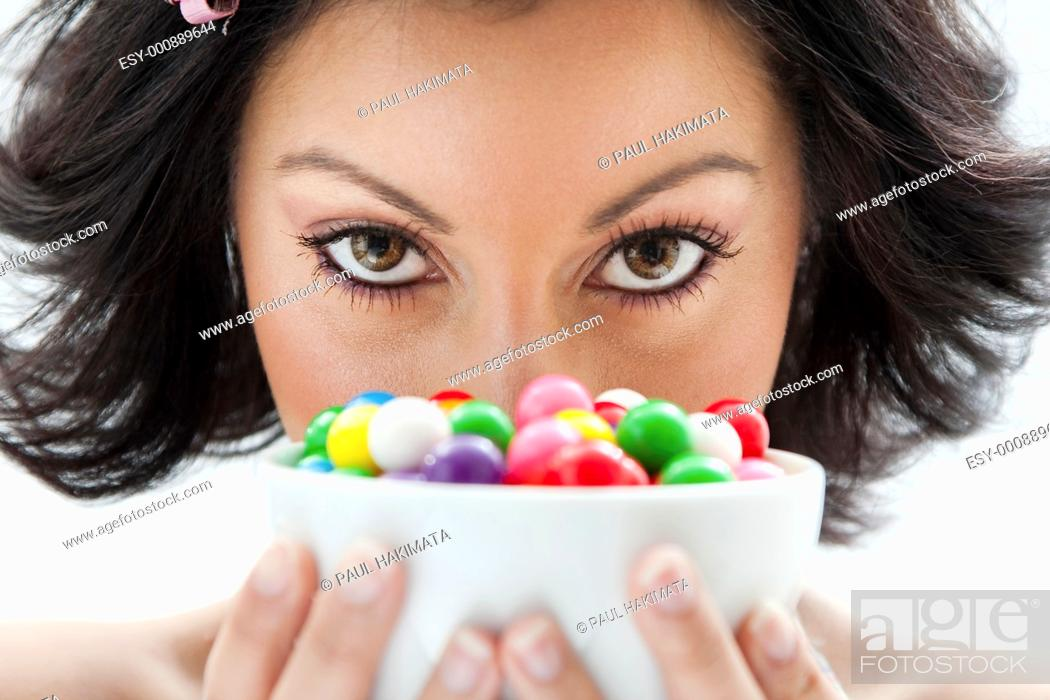 Stock Photo: Beautiful candy girl closeup holding a bowl of colorful bubblegum candy balls in front of her face.
