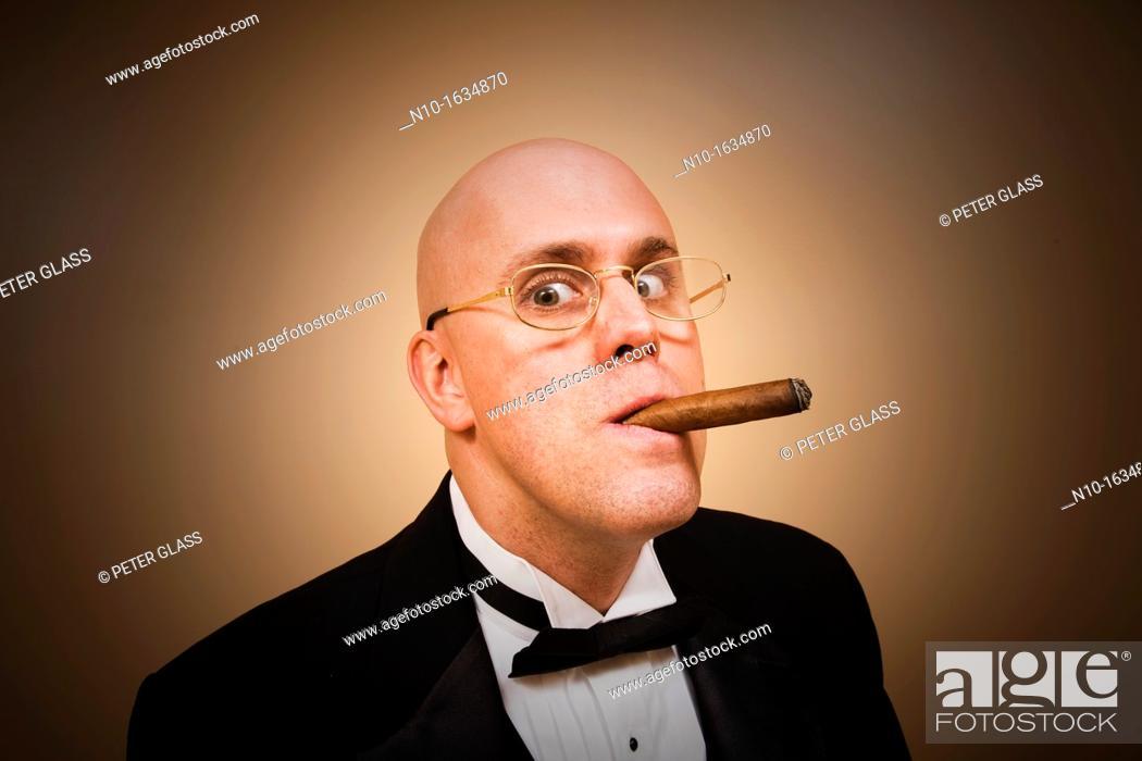 Stock Photo: Middle-age bald man in a tuxedo, smoking a cigar.