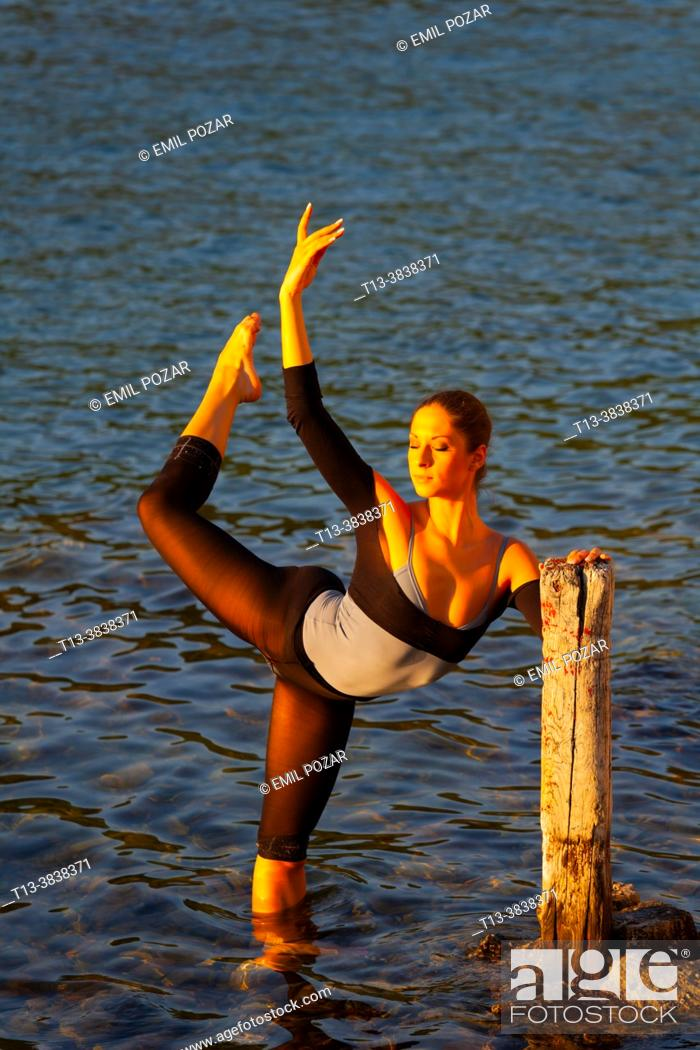 Imagen: Ballerina performing in shallow water lit by warm evening sunset sidelight.