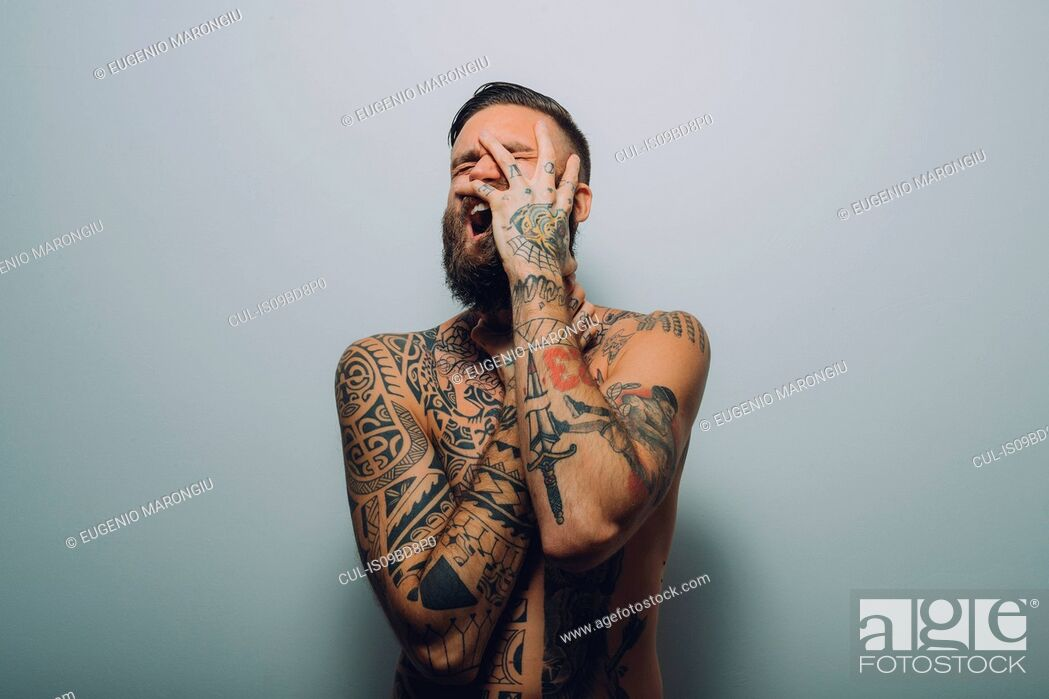 Stock Photo: Portrait of young man with beard, covered in tattoos, hand on face, screaming.