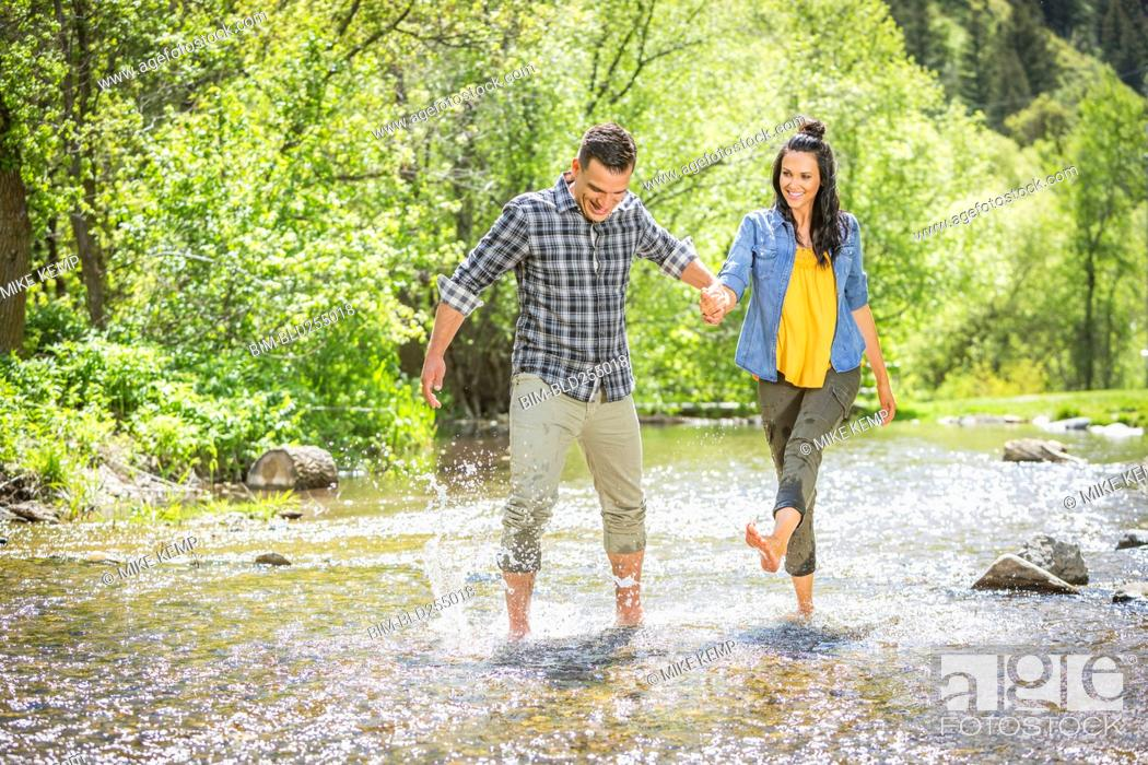 Stock Photo: Woman kicking water on man in river.