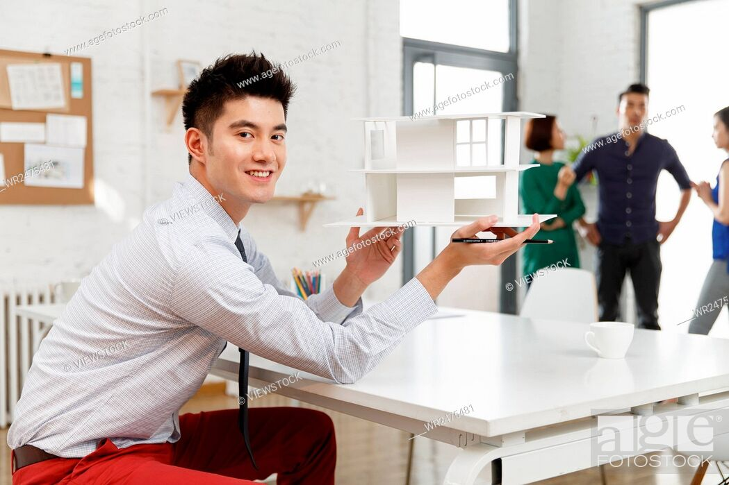 Stock Photo: Business men in the studio with a housing model.