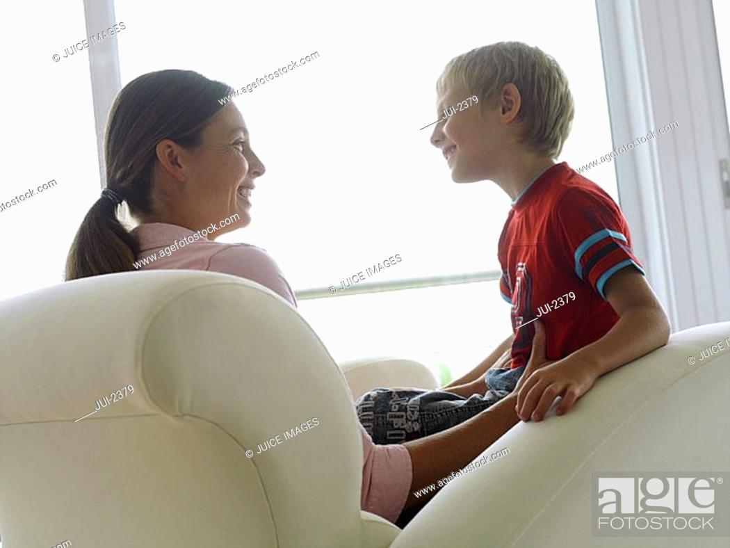 Stock Photo: Mother and son 5-7 sitting in chair at home, smiling, face to face, boy in mother's lap, profile.