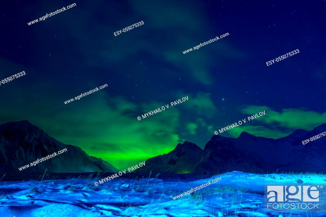 Imagen: Norway. Lofoten. Winter night. Snow-covered grass and mountains. Clouds in the sky and northern lights.