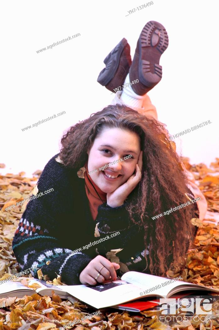 Stock Photo: studio image of teenage girl lying in the autumn leaves smiling at the camera.