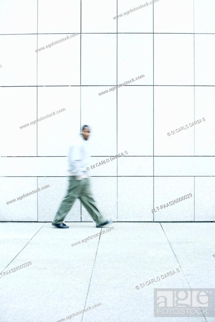 Stock Photo: Man walking with hands in his pockets down sidewalk.