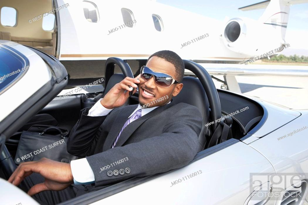 Stock Photo: Man sitting in Convertible near private jet talking on mobile.