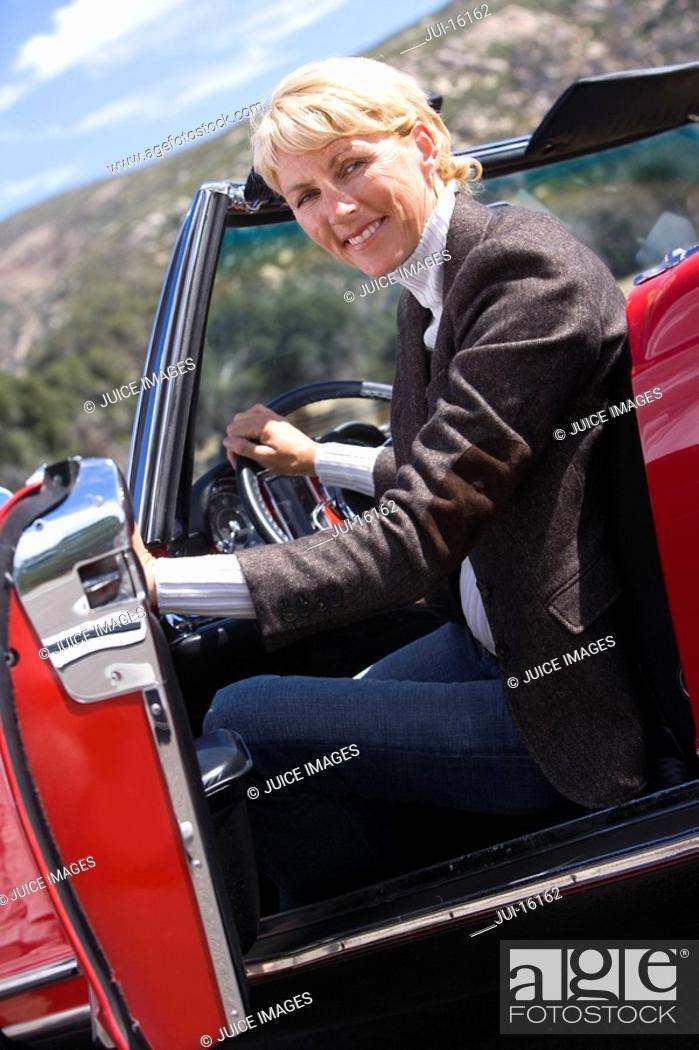 Stock Photo: Senior woman driving red convertible.