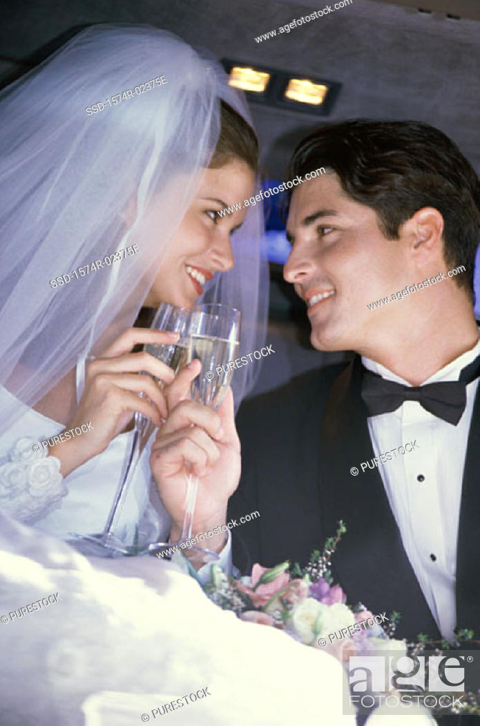 Stock Photo: Newlywed couple toasting with champagne glasses in a car.