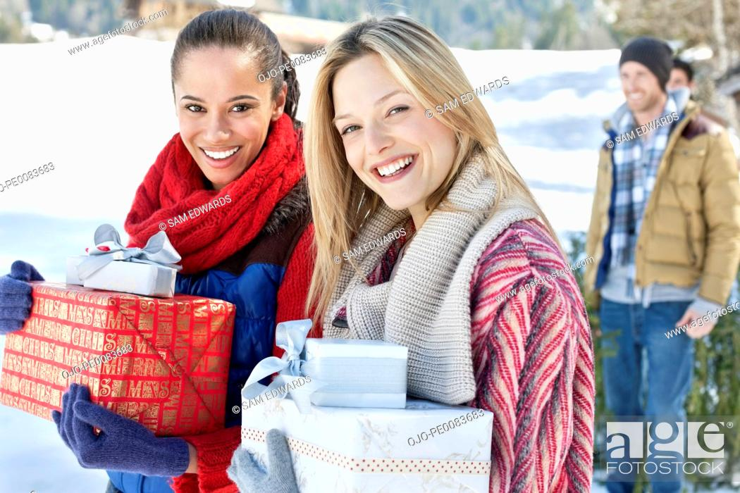 Stock Photo: Portrait of smiling friends with Christmas gifts in snow.