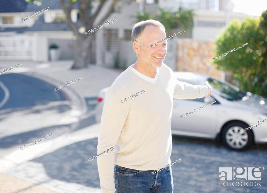 Imagen: Man using keyless lock on car in driveway.
