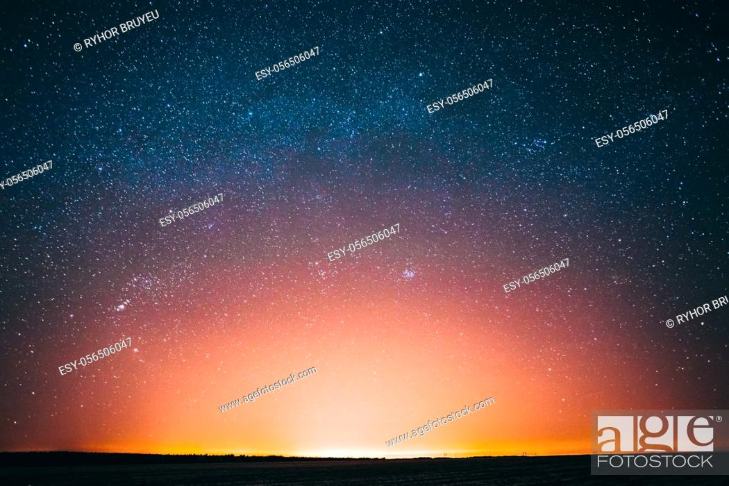 Stock Photo: Amazing Beautiful Night Sky Glowing Stars Background Backdrop With Colorful Sky Gradient. Sunset Sunrise Light And Colourful Night Starry Sky In Blue Yellow.