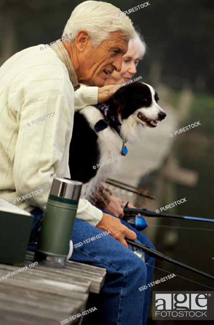 Stock Photo: Side profile of a senior couple fishing on a pier with their dog.