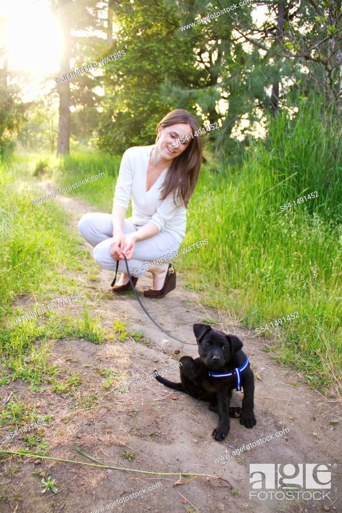 Stock Photo: A young woman outdoors with a black lab puppy in Spokane, Washington, USA.