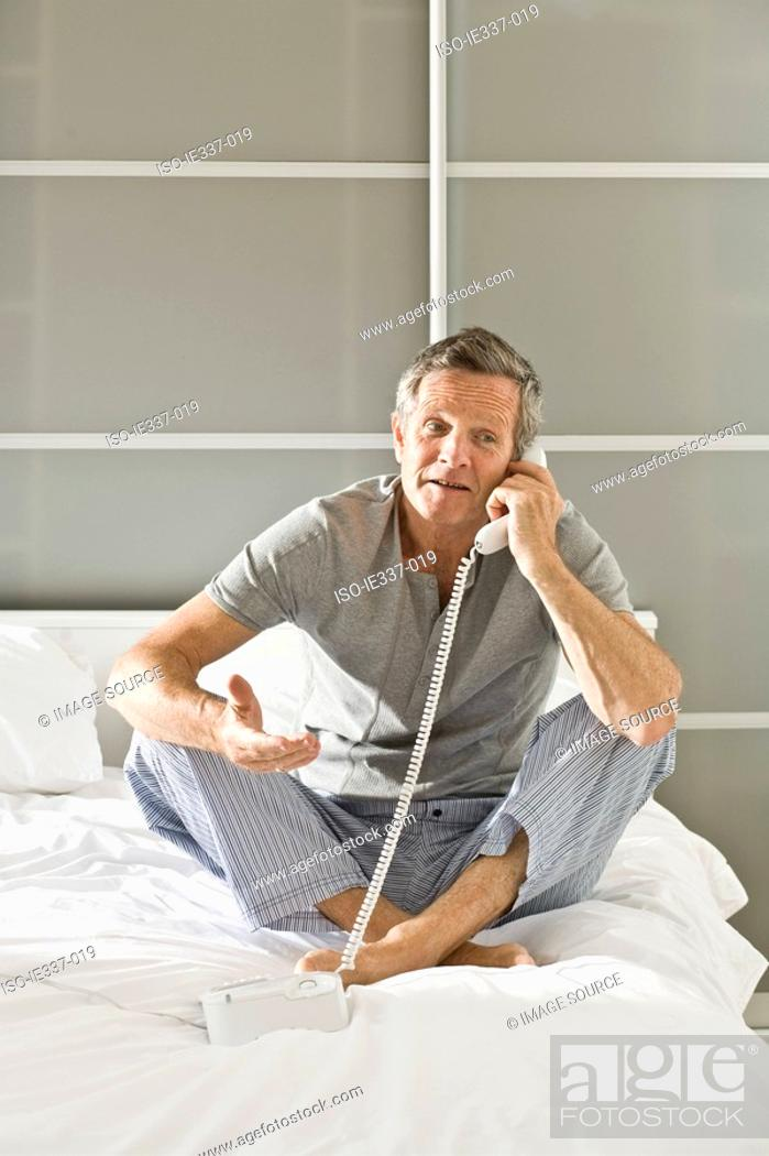 Stock Photo: Man on bed using telephone.