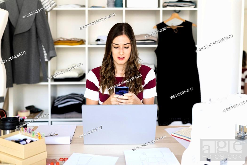 Stock Photo: Female fashion designer using smart phone while sitting with laptop in studio.