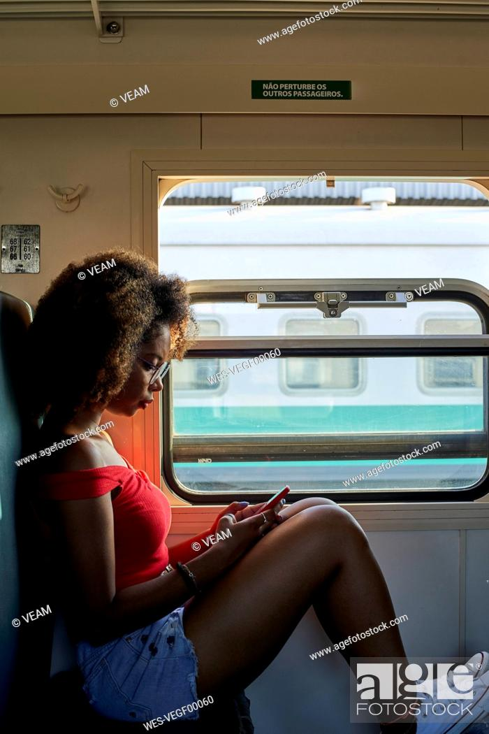 Stock Photo: Young woman on a train checking her phone.