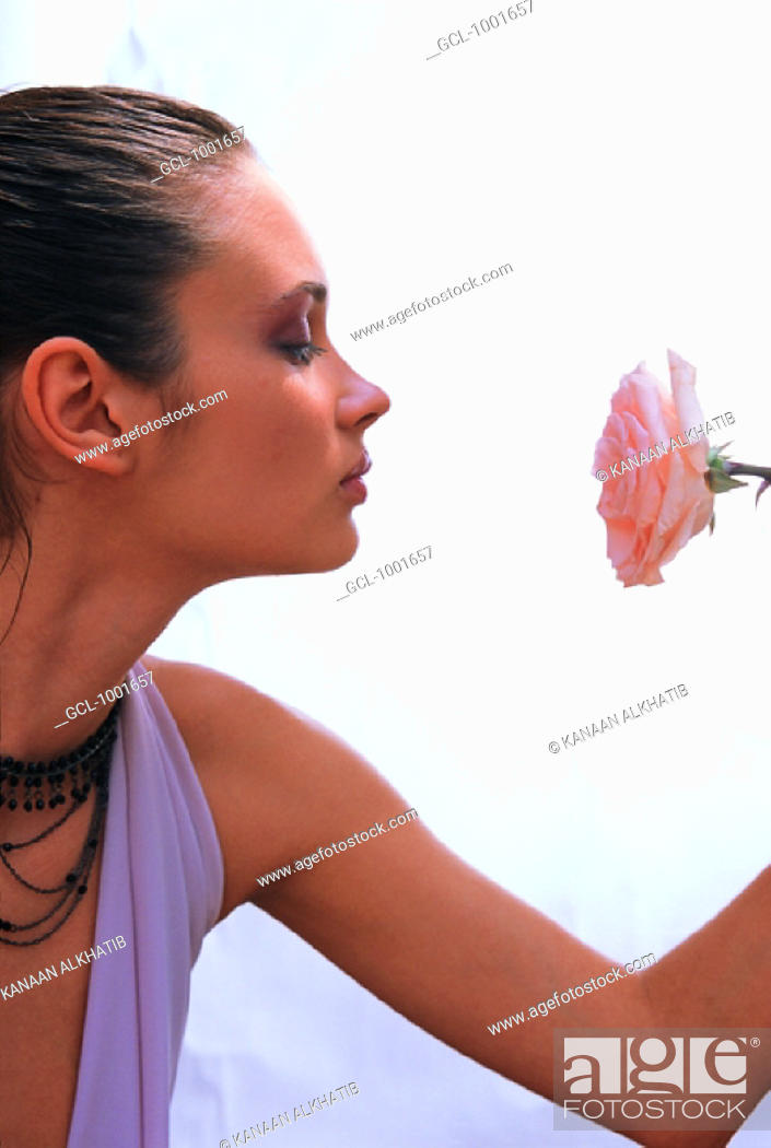 Stock Photo: Woman staring at a rose.
