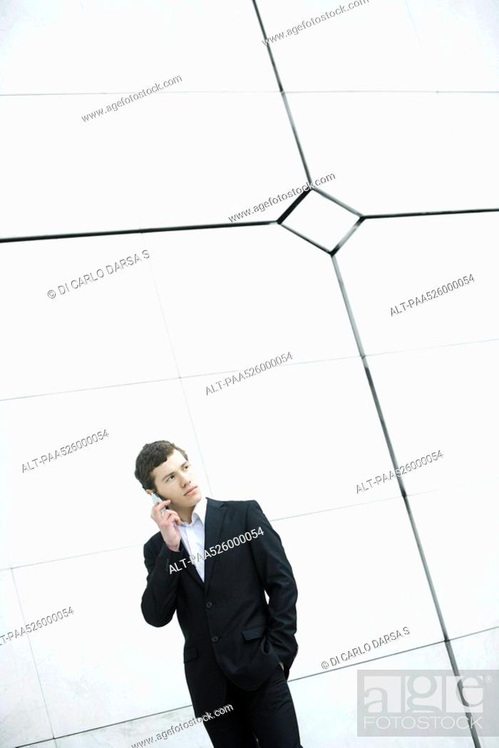 Stock Photo: Businessman using cell phone, hand in pocket, casually standing by wall.