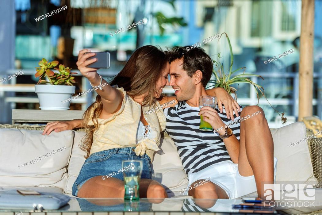 Stock Photo: Happy affectionate young couple taking a selfie on the terrace of a bar.