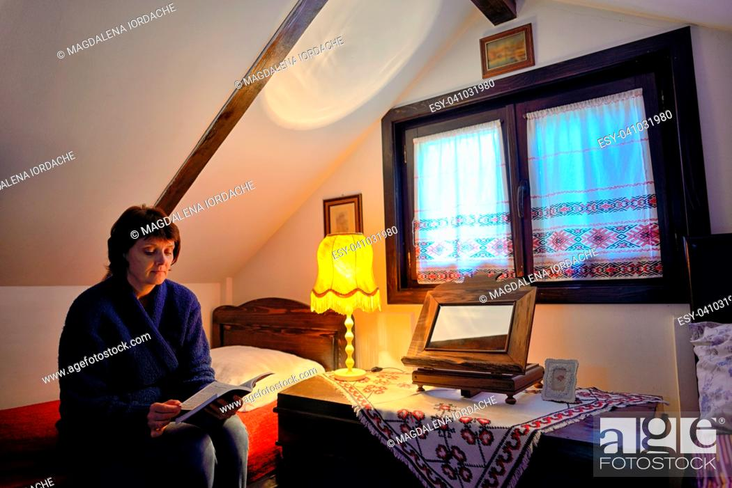 Stock Photo: Female reading book on bed in traditional house.