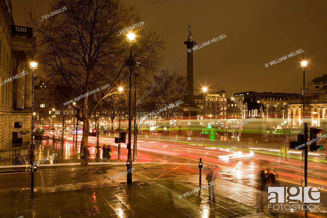 Stock Photo: London, England, Trafalgar Square at night in rain with double-deck busses, people with umbrellas.