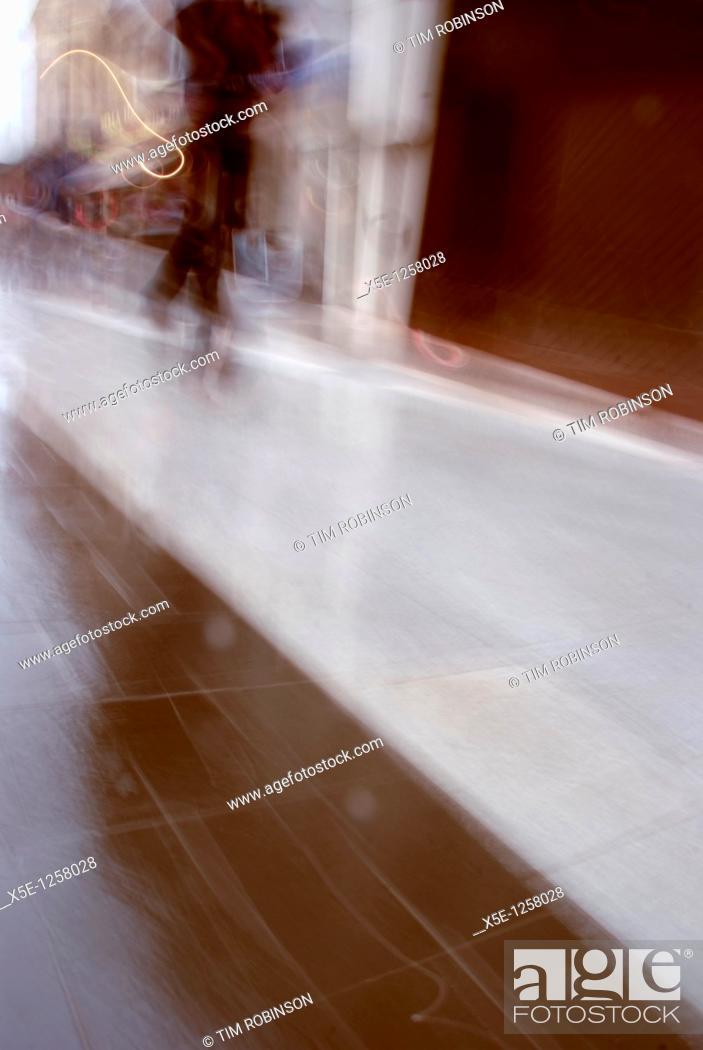 Stock Photo: Blurred figure walking along shopping mall.