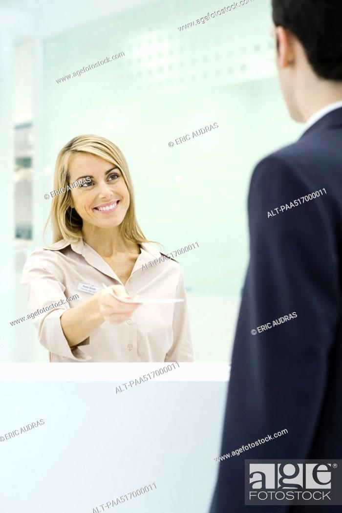 Stock Photo: Professional woman standing behind counter, handing document to businessman.