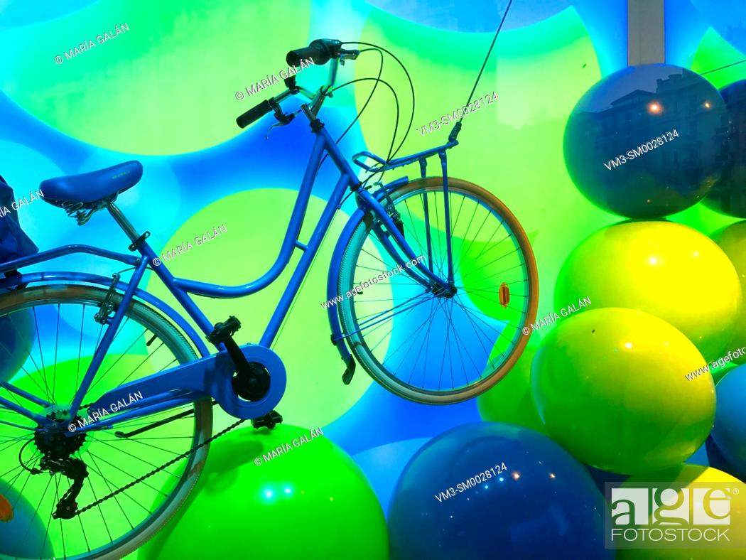 Imagen: Bicycle with green and blueballoons in a shop window. Madrid, Spain.