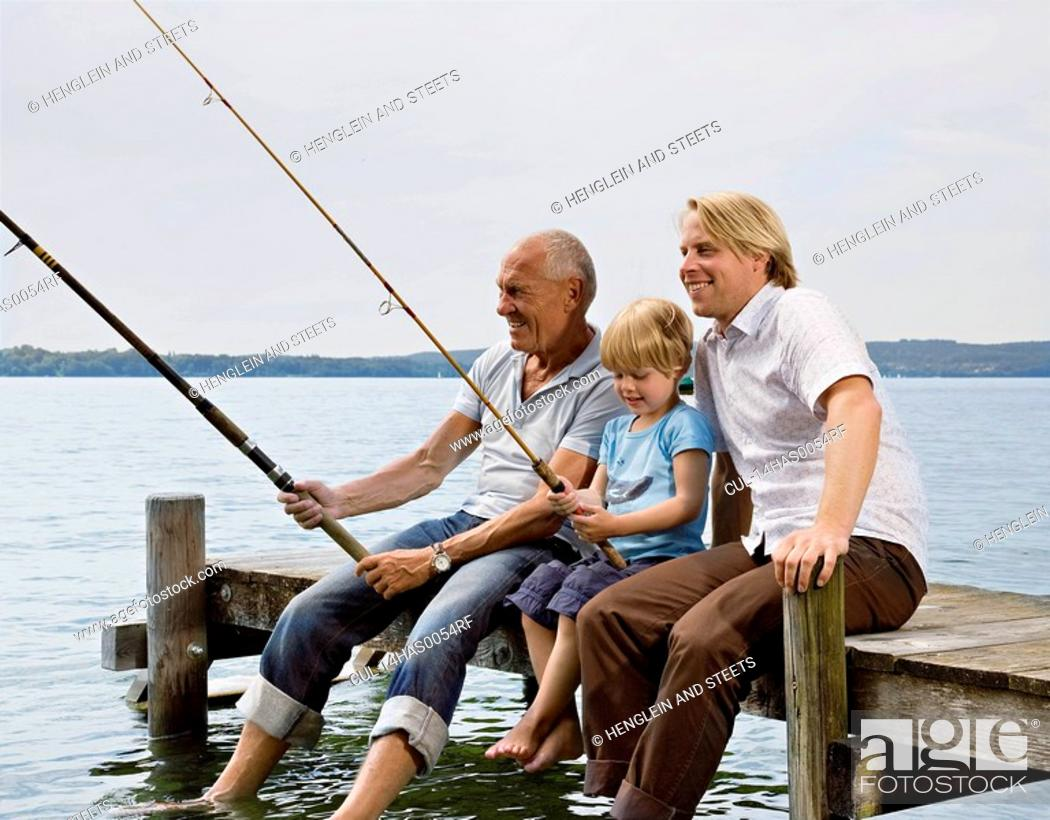 Stock Photo: boy fishing with grandfather, father.