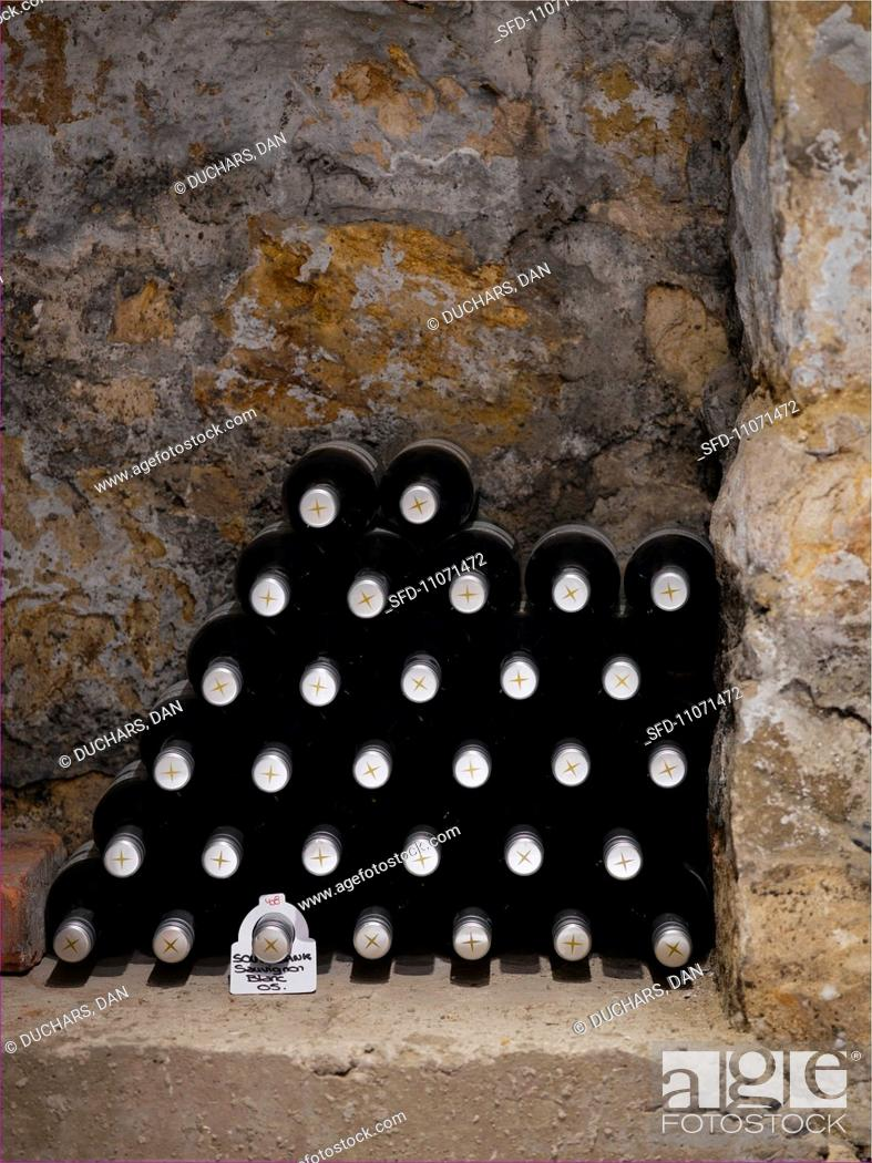 Stock Photo: A stack of wine bottles in a niche in a wall.