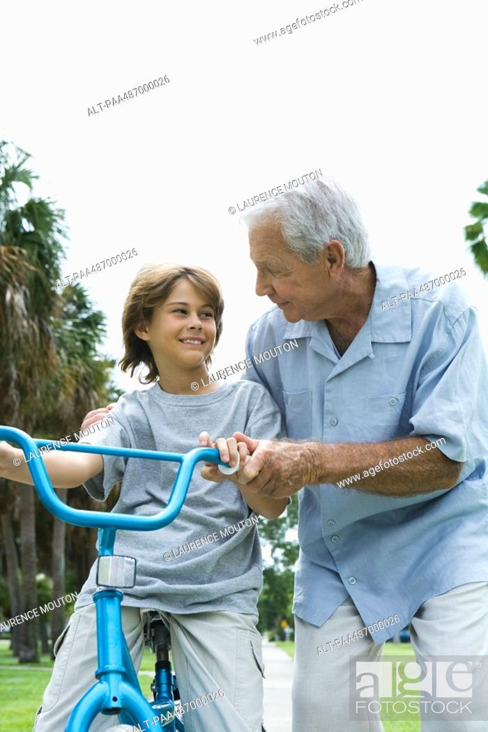 Stock Photo: Grandfather teaching grandson to ride bicycle, front view.