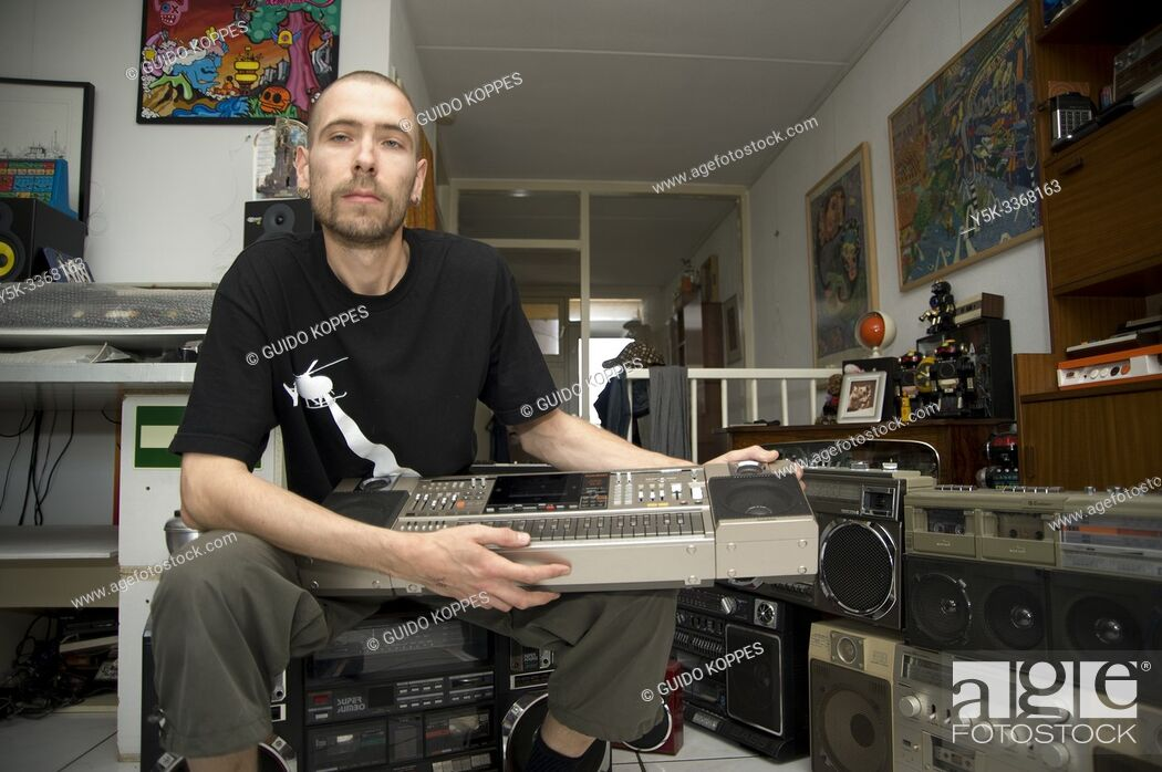 Photo de stock: Rotterdam, Netherlands. Alternative, adult male showing off his collections of boom machines and ghetto blasters inside his residential living room.