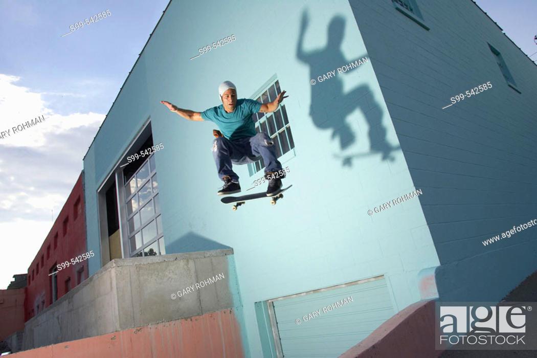 Stock Photo: Skater skateboarding behind a building in downtown Kansas City, Missouri, USA.