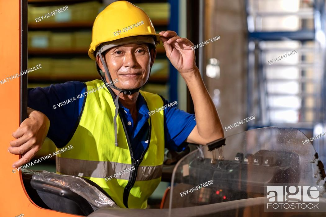 Stock Photo: Portrait asian male warehouse worker using forklift truckin large warehouse distribution center. Business warehouse storage transportation and logistic concept.