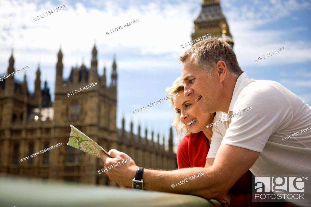 Stock Photo: A middle-aged couple standing near the Houses of Parliament, looking at a map.