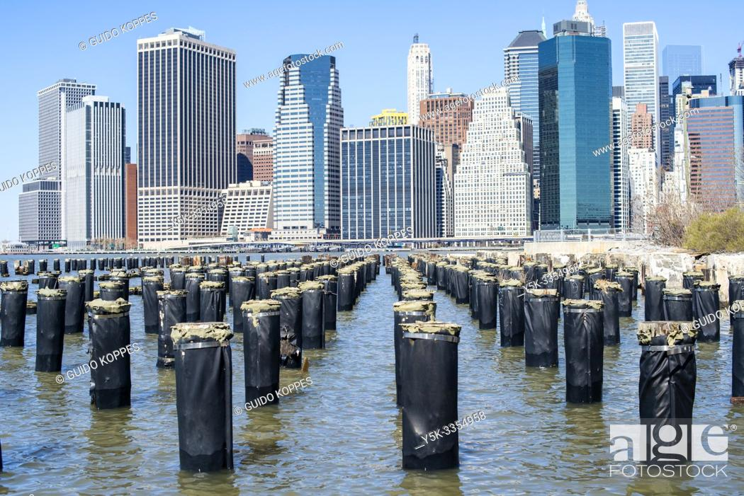 Stock Photo: New York City, USA. View on the remains of a harbor pier and the Skyline of down town Manhattan from Brooklyn Bridge Park / Pier 1.