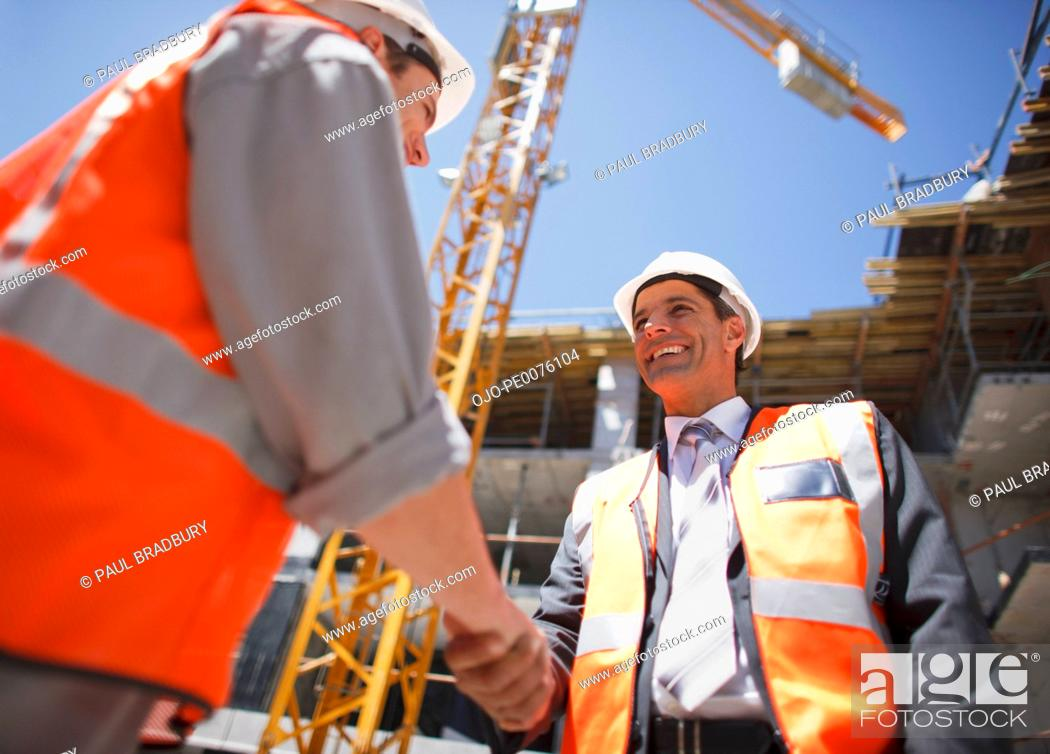 Stock Photo: Construction workers shaking hands on construction site.