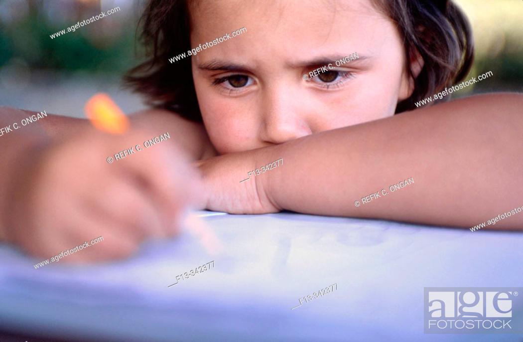 Stock Photo: 8 years old girl studying homework.