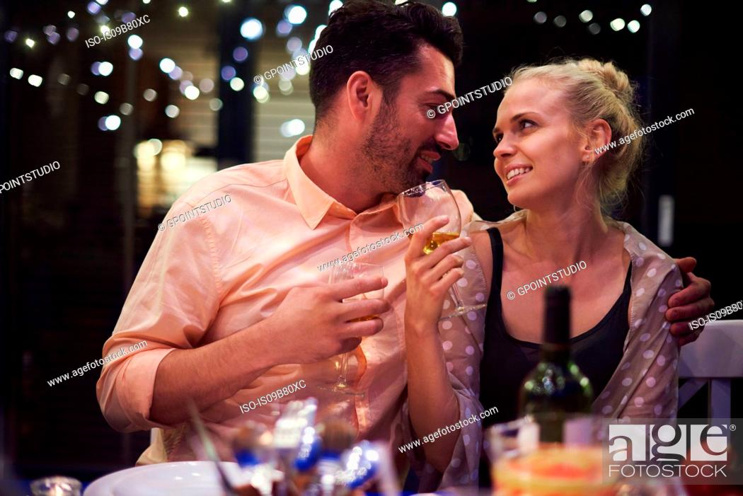 Stock Photo: Couple sitting at table, holding wine glasses, face to face, smiling.