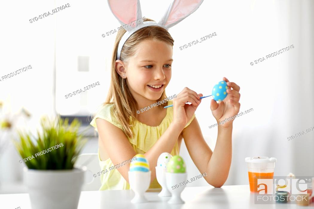Stock Photo: happy girl coloring easter eggs at home.