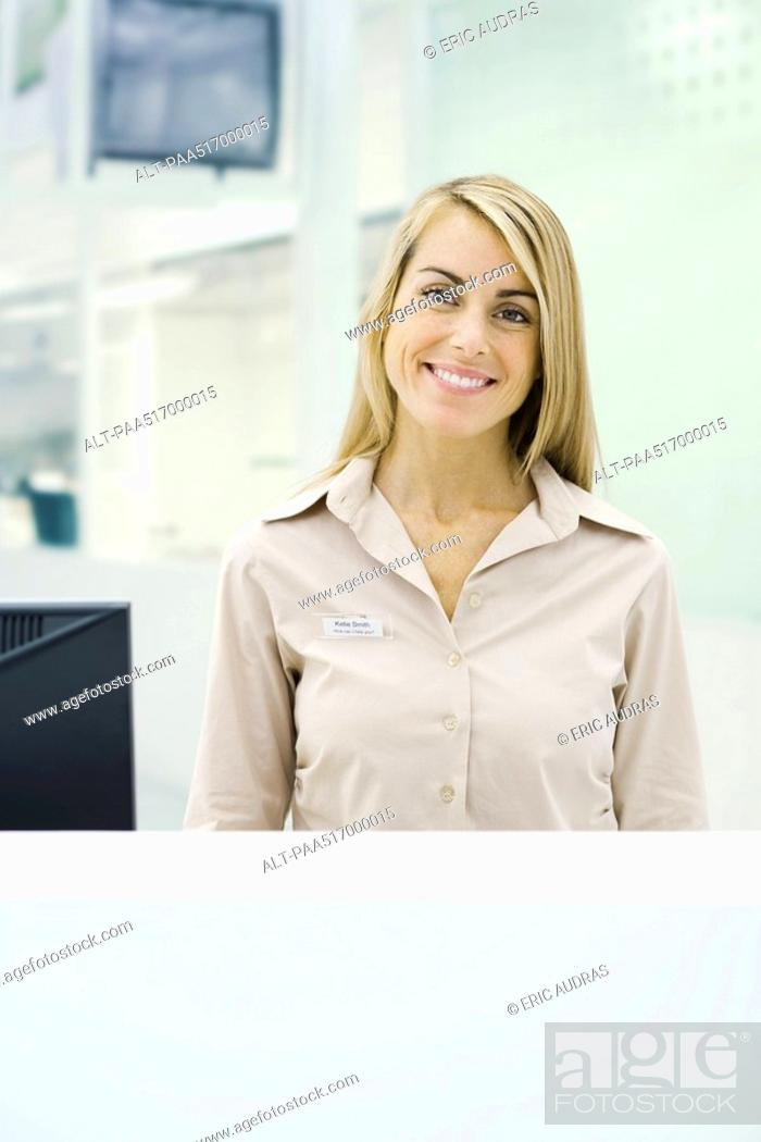 Stock Photo: Businesswoman standing behind counter, smiling at camera, portrait.