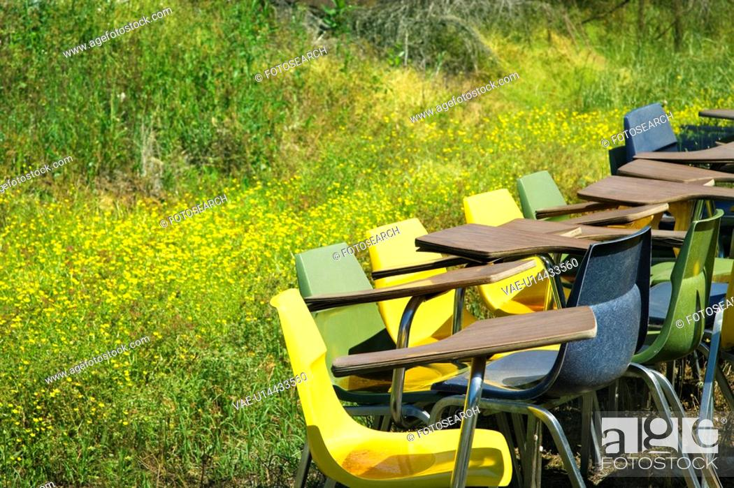 Stock Photo: Bunch of old school chairs in grassy field.