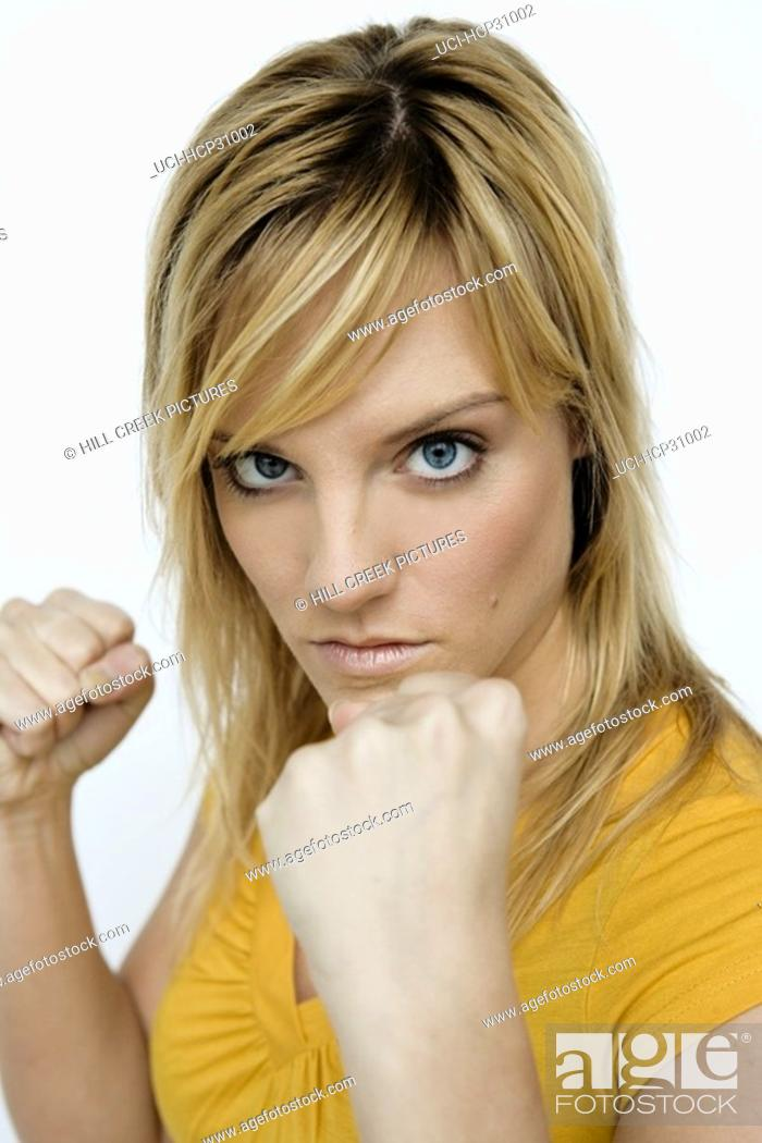 Stock Photo: Young woman with fists up, readying to fight.