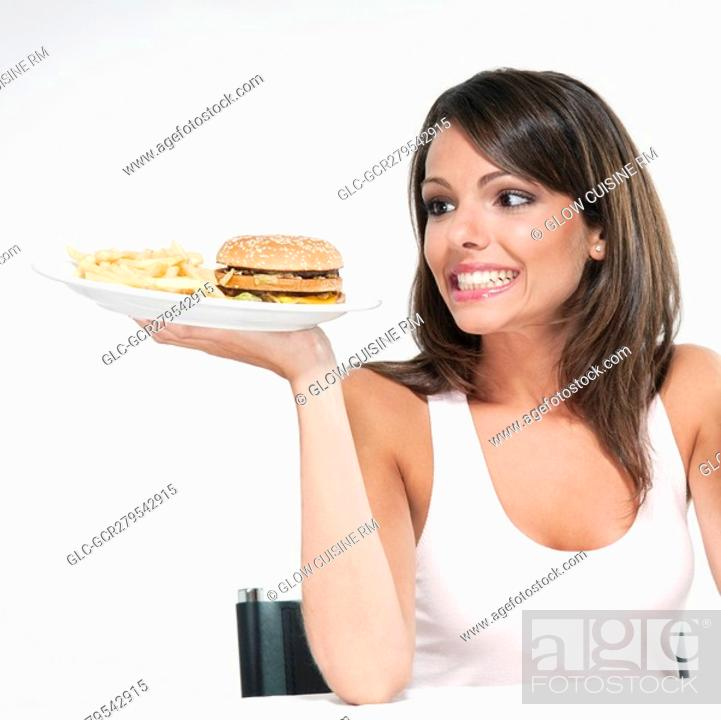 Stock Photo: Woman holding a hamburger plate and smiling.