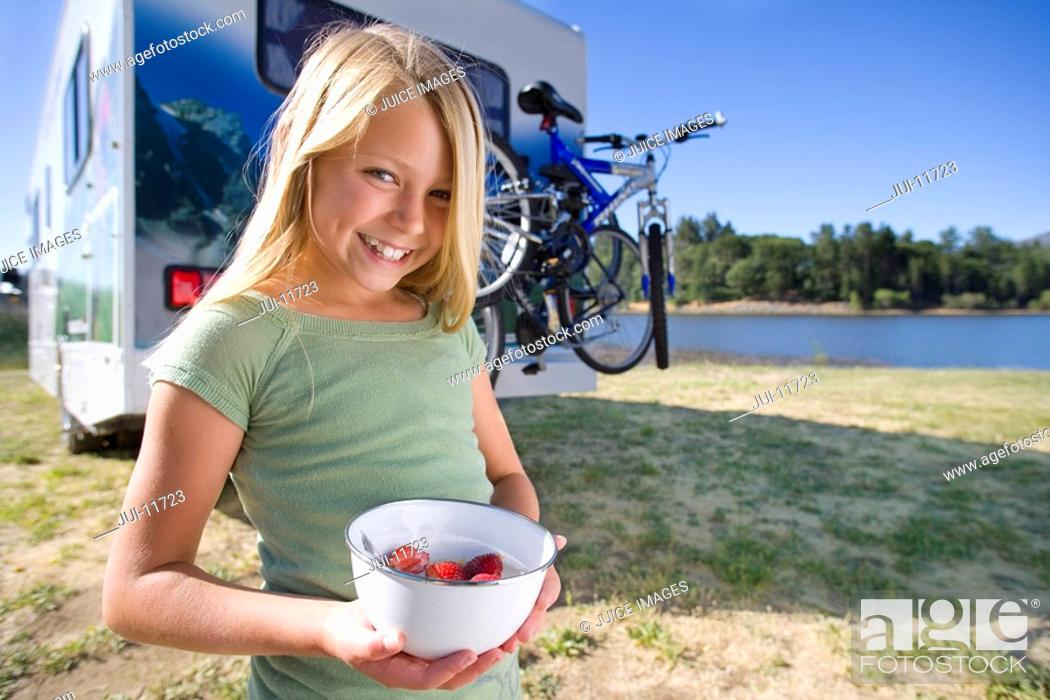 Stock Photo: Girl 8-10 with bowl of strawberries by motor home and lake, smiling, portrait.